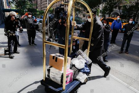 Personal belongings delivered from the vehicle Michael Cohen arrived in are brought into his Manhattan apartment building, in New York.President Donald Trump's longtime personal lawyer and fixer was released federal prison Thursday and is expected to serve the remainder of his sentence at home. Cohen has been serving a federal prison sentence at FCI Otisville in New York after pleading guilty to numerous charges, including campaign finance fraud and lying to Congress