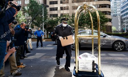 A doorman brings in items belonging to Michael Cohen, President Donald Trump's former lawyer, at his apartment building after Cohen was released on furlough today from federal prison because of the coronavirus to serve the rest of his sentence under home confinement in New York, New York, USA, 21 May 2020. Cohen plead guilty last May to federal charges including campaign finance fraud and lying to Congress and was originally scheduled to be released from prison in November 2021.