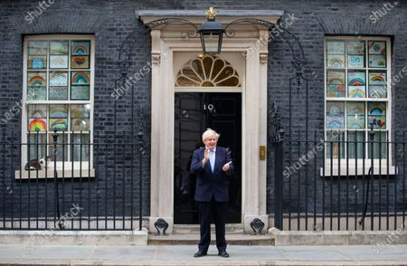 Stock Image of UK Prime Minister, Boris Johnson, claps for the NHS and social care workers on the step of 10 Downing Street. Larry the Downing Street cat sits on the ledge.