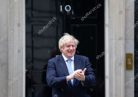 UK Prime Minister, Boris Johnson, claps for the NHS and social care workers on the step of 10 Downing Street.