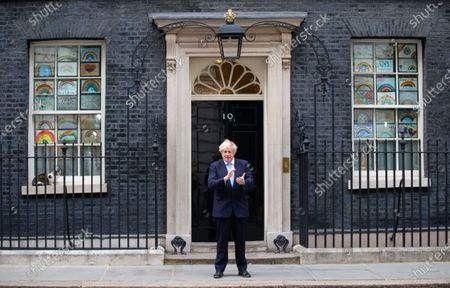 UK Prime Minister, Boris Johnson, claps for the NHS and social care workers on the step of 10 Downing Street. Larry the Downing Street cat sits on the ledge.