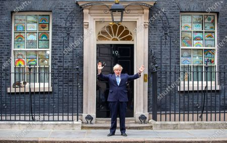 Stock Photo of UK Prime Minister, Boris Johnson, claps for the NHS and social care workers on the step of 10 Downing Street. Larry the Downing Street cat sits on the ledge.