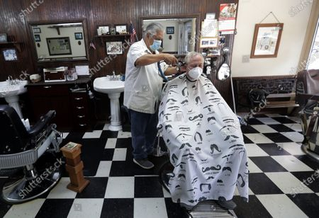 Barber Rudy Soliz gives Brian Barnett a haircut at the San Marcos Barber Shop in San Marcos, Texas, . Businesses in Texas closed due to the COVID-19 pandemic continue to open in phases; bars will be permitted to open Friday