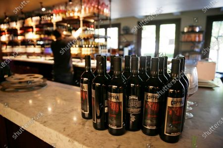 Bottles of Apocalypse Now Red Blend wine are seen on a tasting bar counter as Jesse Cierly restocks a shelf at the Francis Ford Coppola Winery, in Geyserville, Calif. The winery has been closed the past two months because of the coronavirus threat and is preparing to reopen to visitors, possibly in the next few days once approval comes