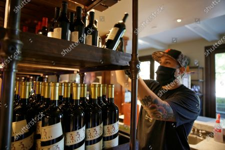 Jesse Cierly stocks a tasting bar shelf with bottles of wine at the Francis Ford Coppola Winery, in Geyserville, Calif. The winery has been closed the past two months because of the coronavirus threat and is preparing to reopen to visitors, possibly in the next few days once approval comes