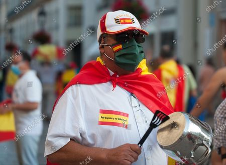A man wearing a face mask as a preventive measure makes noise with a pan during the demonstration. Several Spaniards have protested against the Spanish government and public management of the Covid - 19 crisis. The far-right party VOX demand the end of confinement and state of emergency because they consider that limit their rights and all Spaniards.