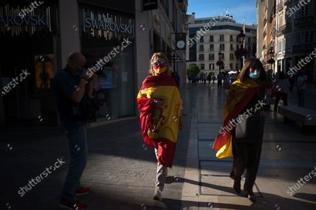 Women wrapped with Spanish flags walk on the street as they take part during the protest. Several Spaniards have protested against the Spanish government and public management of the Covid - 19 crisis. The far-right party VOX demand the end of confinement and state of emergency because they consider that limit their rights and all Spaniards.
