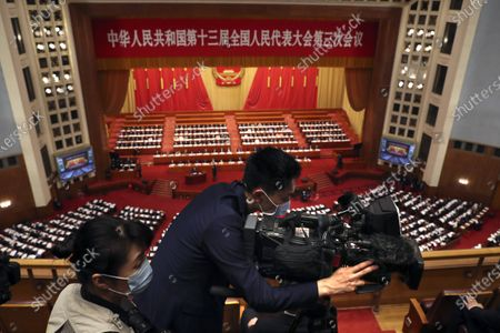 Videographer wearing a face mask to protect against the new coronavirus films during the opening session of China's National People's Congress (NPC) at the Great Hall of the People in Beijing