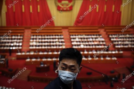 Staff member wearing a face mask to protect against the new coronavirus stands during the opening session of China's National People's Congress (NPC) at the Great Hall of the People in Beijing