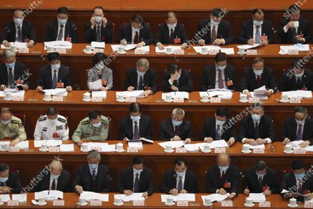 Delegates read a government work report during the opening session of China's National People's Congress (NPC) at the Great Hall of the People in Beijing