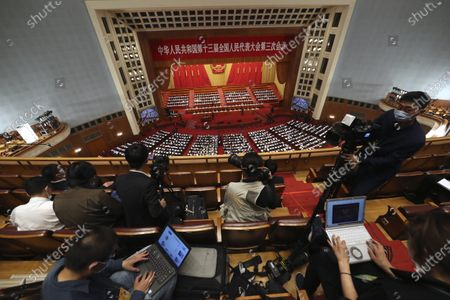 Journalists wearing face masks to protect agains the new coronavirus cover the opening session of China's National People's Congress (NPC) at the Great Hall of the People in Beijing