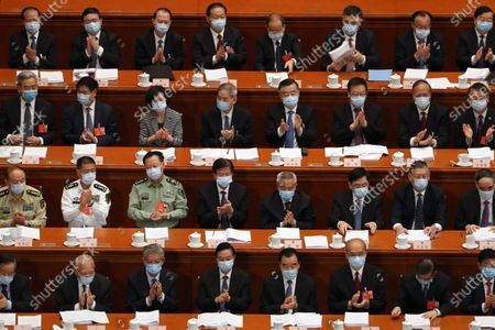 Delegates applaud during the opening session of China's National People's Congress (NPC) at the Great Hall of the People in Beijing