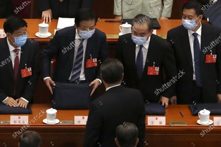 Chinese Foreign Minister Wang Yi, second from right, talks with Chinese President Xi Jinping, center, after the opening session of China's National People's Congress (NPC) at the Great Hall of the People in Beijing