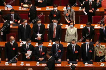 Delegates stand as Chinese President Xi Jinping, bottom center, leaves after the opening session of China's National People's Congress (NPC) at the Great Hall of the People in Beijing