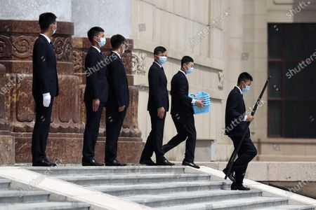 Security officers wearing face masks to protect against the new coronavirus wear face masks as they stand on the steps of the Great Hall of the People after the opening session of China's National People's Congress (NPC) in Beijing