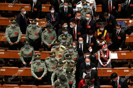 Military delegates leave after the opening session of China's National People's Congress (NPC) at the Great Hall of the People in Beijing