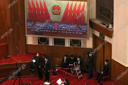 Staff members sit under a large video screen during the opening session of China's National People's Congress (NPC) at the Great Hall of the People in Beijing