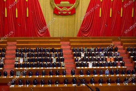 Chinese leaders and delegates bow their heads during the opening session of China's National People's Congress (NPC) at the Great Hall of the People in Beijing