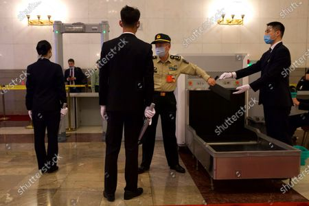 Military delegate goes through a security check before the opening session of China's National People's Congress (NPC) at the Great Hall of the People in Beijing