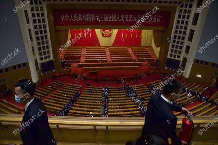 Chinese security officials stand guard after the opening session of China's National People's Congress (NPC) at the Great Hall of the People in Beijing