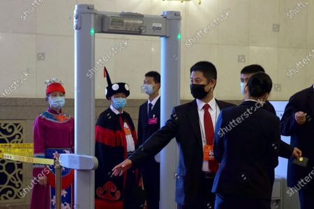 Delegates and officials go through a security check before the opening session of China's National People's Congress (NPC) at the Great Hall of the People in Beijing