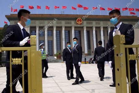 Chinese security officials wear face masks to protect against the new coronavirus as they stand guard outside the Great Hall of the People after the opening session of China's National People's Congress (NPC) in Beijing