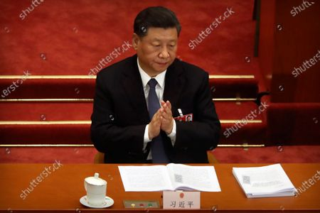 Chinese President Xi Jinping applauds during the opening session of China's National People's Congress (NPC) at the Great Hall of the People in Beijing