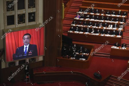 Video screen shows Chinese Premier Li Keqiang as he delivers the government work report during the opening session of China's National People's Congress (NPC) at the Great Hall of the People in Beijing