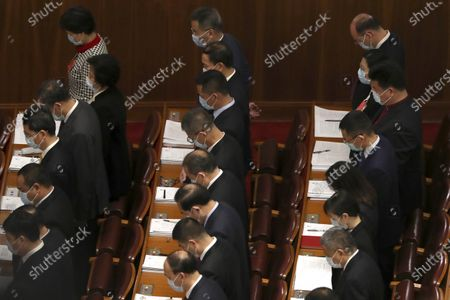 Delegates bow their heads during the opening session of China's National People's Congress (NPC) at the Great Hall of the People in Beijing