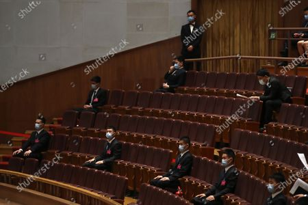 Security officers wearing face masks to protect against the new coronavirus sit on guard during the opening session of China's National People's Congress (NPC) at the Great Hall of the People in Beijing