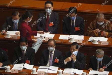An attendant wearing a face mask to protect against the new coronavirus refills cups for delegates during the opening session of China's National People's Congress (NPC) at the Great Hall of the People in Beijing