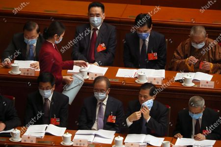 An attendant wearing a face mask refills glasses for delegates during the opening session of China's National People's Congress (NPC) at the Great Hall of the People in Beijing, China, 22 May 2020. China held the Chinese People's Political Consultative Conference (CPPCC) on 21 May and will hold the National People's Congress (NPC) on 22 May, after the two major political meetings initially planned to be held in March 2020 were postponed amid the ongoing coronavirus COVID-19 pandemic.