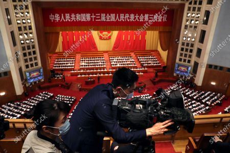 A videographer wearing a face mask films during the opening session of China's National People's Congress (NPC) at the Great Hall of the People in Beijing, China, 22 May 2020. China held the Chinese People's Political Consultative Conference (CPPCC) on 21 May and will hold the National People's Congress (NPC) on 22 May, after the two major political meetings initially planned to be held in March 2020 were postponed amid the ongoing coronavirus COVID-19 pandemic.