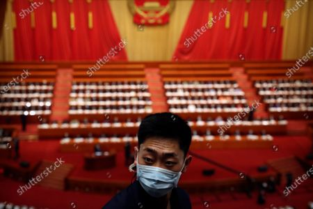 A staff member wearing a face mask stands uring the opening session of China's National People's Congress (NPC) at the Great Hall of the People in Beijing, China, 22 May 2020. China held the Chinese People's Political Consultative Conference (CPPCC) on 21 May and will hold the National People's Congress (NPC) on 22 May, after the two major political meetings initially planned to be held in March 2020 were postponed amid the ongoing coronavirus COVID-19 pandemic.