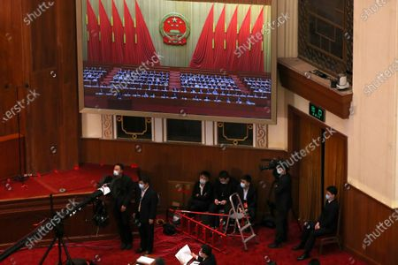 Staff members sit under a large video screen during the opening session of China's National People's Congress (NPC) at the Great Hall of the People in Beijing, China, 22 May 2020. China held the Chinese People's Political Consultative Conference (CPPCC) on 21 May and will hold the National People's Congress (NPC) on 22 May, after the two major political meetings initially planned to be held in March 2020 were postponed amid the ongoing coronavirus COVID-19 pandemic.