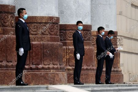 Security officers wearing face masks stand on the steps of the Great Hall of the People after the opening session of China's National People's Congress (NPC) at the Great Hall of the People in Beijing, China, 22 May 2020. China held the Chinese People's Political Consultative Conference (CPPCC) on 21 May and will hold the National People's Congress (NPC) on 22 May, after the two major political meetings initially planned to be held in March 2020 were postponed amid the ongoing coronavirus COVID-19 pandemic.