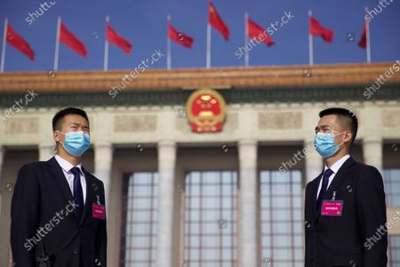 Chinese security officials wear face masks for protection against the coronavirus as they stand guard outside the Great Hall of the People before the opening session of China's National People's Congress (NPC) in Beijing, China, 22 May 2020. China held the Chinese People's Political Consultative Conference (CPPCC) on 21 May and will hold the National People's Congress (NPC) on 22 May, after the two major political meetings initially planned to be held in March 2020 were postponed amid the ongoing coronavirus COVID-19 pandemic.
