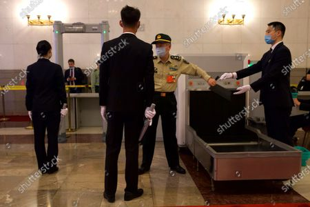 A military delegate goes through a security check before the opening session of China's National People's Congress (NPC) at the Great Hall of the People in Beijing, China, 22 May 2020. China held the Chinese People's Political Consultative Conference (CPPCC) on 21 May and will hold the National People's Congress (NPC) on 22 May, after the two major political meetings initially planned to be held in March 2020 were postponed amid the ongoing coronavirus COVID-19 pandemic.