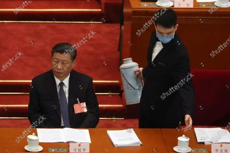 An attendant wearing a face mask refills a glass next to Chinese President Xi Jinping (L) during the opening session of China's National People's Congress (NPC) at the Great Hall of the People in Beijing, China, 22 May 2020. China held the Chinese People's Political Consultative Conference (CPPCC) on 21 May and will hold the National People's Congress (NPC) on 22 May, after the two major political meetings initially planned to be held in March 2020 were postponed amid the ongoing coronavirus COVID-19 pandemic.