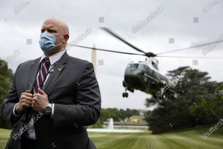 Stock Image of A United States Secret Service agent stands guard as Marine One with US President Donald J. Trump on board arrives on the South Lawn of the White House in Washington, DC.