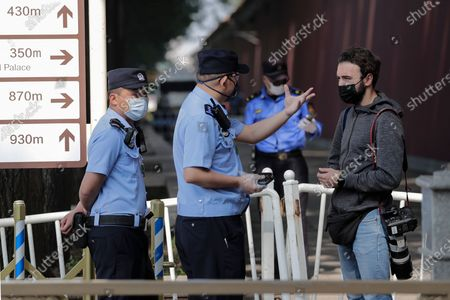 Foreign journalist is stopped by policemen as he tries to film the delegates' buses arrive to the Great Hall of the People to attend the opening session of China's National People's Congress (NPC) in Beijing
