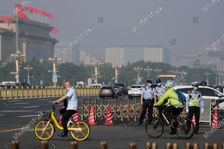 Cyclists ride past policemen blocked the cycling path leading to the Great Hall of the People and Tiananmen Square as delegates arrive to attend the opening session of China's National People's Congress (NPC) in Beijing, . China's top economic official on Friday promised higher spending to revive its coronavirus-battered economy and curb surging job losses and said Beijing would set no growth target in order to focus on fighting the disease