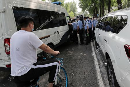 Masked cyclist looks at policemen getting on to a police van near the Great Hall of the People during the opening session of China's National People's Congress (NPC) in Beijing, . China's top economic official on Friday promised higher spending to revive its coronavirus-battered economy and curb surging job losses and said Beijing would set no growth target in order to focus on fighting the disease
