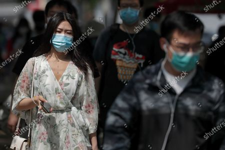 People wearing face masks to protect against the spread of the new coronavirus walk on a street in Beijing, . China's top economic official on Friday promised higher spending to revive its coronavirus-battered economy and curb surging job losses and said Beijing would set no growth target in order to focus on fighting the disease