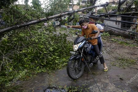 Motorists make their way through damaged cables and a tree branch fallen in the middle of a road after Cyclone Amphan hit the region in Kolkata, India, . People forgot about social distancing and crammed themselves into government shelters, minutes before Cyclone Amphan crashed in West Bengal. The cyclone killed dozens of people and the coronavirus nine in this region, one of India's poorer states. Even before the cyclone, its pandemic response was lagging; the state has one of the highest fatality rates from COVID-19 in India. With an economy crippled by India's eight-week lockdown, and health care systems sapped by the virus, authorities must tackle both COVID-19 and the cyclone's aftermath