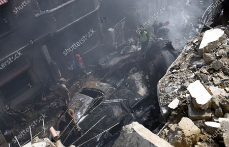Locals inspect the wreckage of a passenger plane of state run Pakistan International Airlines, at the scene after crashed on a residential colony, in Karachi, Pakistan, 22 May 2020. A PIA Airbus A-320 flight from Lahore to Karachi carrying some 107 passengers and crew, crashed while landing in Karachi on 22 May.