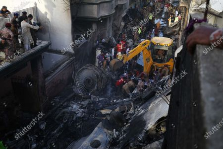 Officials try to salvage the wreckage of the passenger plane of state run Pakistan International Airlines, at the crash scene in a residential area, in Karachi, Pakistan, 22 May 2020. A Pakistan International Airlines passenger flight with over 100 people on board crashed on 22 May as it was about to land near a residential area close to the airport in the port city of Karachi, a civil aviation official said.