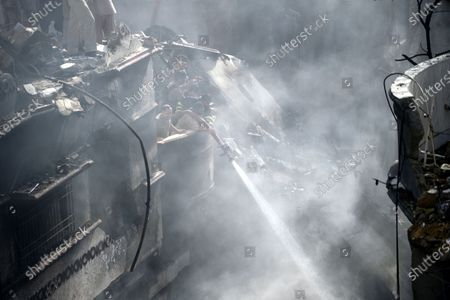Firefighters douse the smouldering wreckage of the passenger plane of state run Pakistan International Airlines, at the crash scene of a residential area, in Karachi, Pakistan, 22 May 2020. A Pakistan International Airlines passenger flight with over 100 people on board crashed on 22 May as it was about to land near a residential area close to the airport in the port city of Karachi, a civil aviation official said.