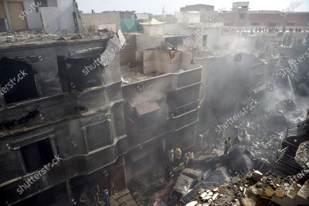 Officials inspect the wreckage of the passenger plane of state run Pakistan International Airlines, at the crash scene of a residential area, in Karachi, Pakistan, 22 May 2020. A Pakistan International Airlines passenger flight with over 100 people on board crashed on 22 May as it was about to land near a residential area close to the airport in the port city of Karachi, a civil aviation official said.