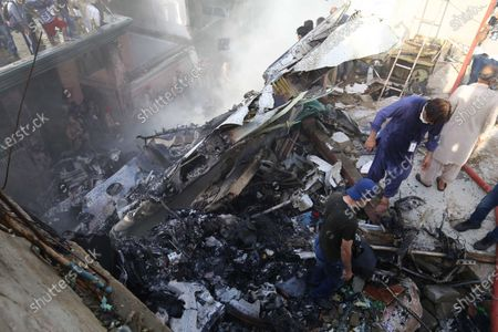 Rescue workers search for the bodies or survivors amid wreckage of the passenger plane of state run Pakistan International Airlines, after it crashed on a residential colony, in Karachi, Pakistan, 22 May 2020. A Pakistan International Airlines passenger flight with over 100 people on board crashed on 22 May as it was about to land near a residential area close to the airport in the port city of Karachi, a civil aviation official said.